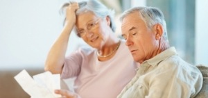 Distressed elderly couple reading insurance paperwork