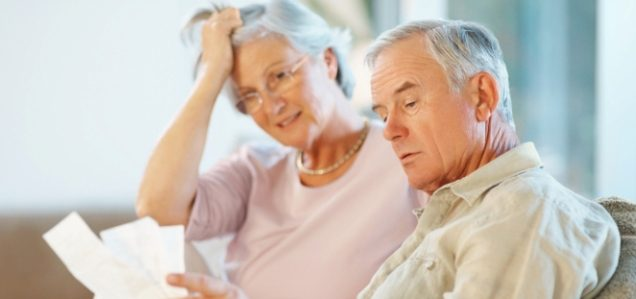 Distressed elderly couple reading paperwork