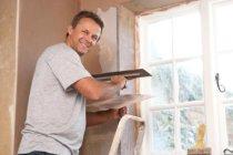 Plasterer repairing damaged walls